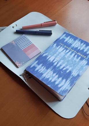 Protector de cadernos ou tablets manufacturado com tons suaves de flores da primaver, duas canetas roller ball e um bloco de post its de vários tamanhos